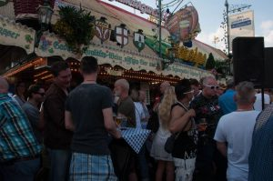 Party goers in front of a funfair stall
