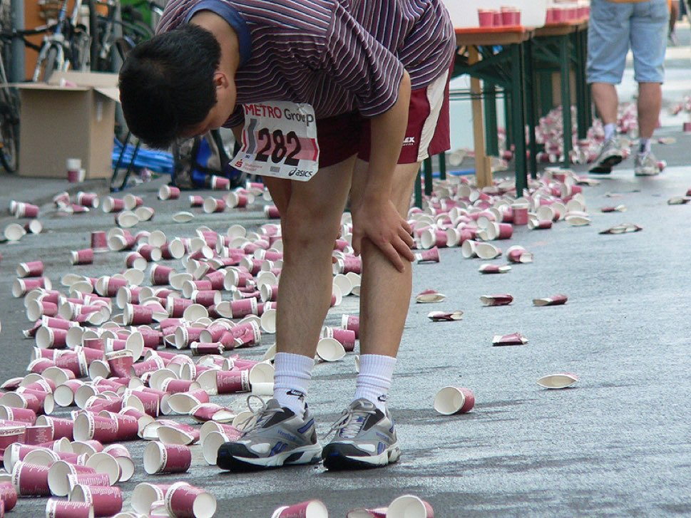 Marathon runner taking pause among water cups