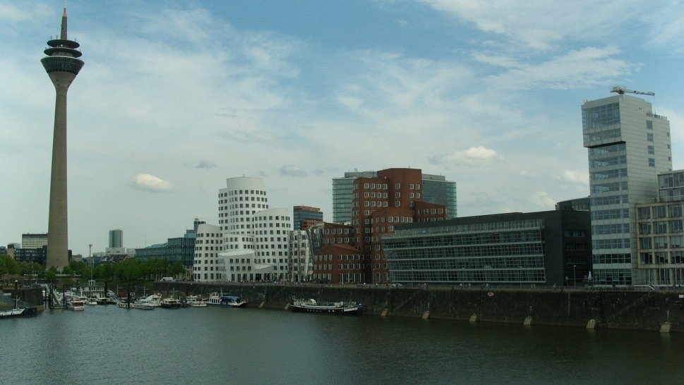 View over water with harbour buildings and tower